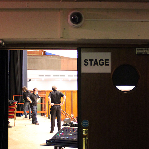 A wired dome camera, this time mounted flat on the wall above the stage door.